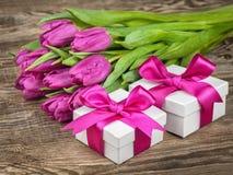 Tulipa, caixas de presente com curva violeta na placa de madeira Imagens de Stock