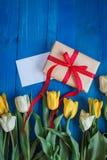 A tulipa da mola floresce, caixa de presente e o cartão de papel na tabela de madeira azul de cima no plano coloca o estilo Imagem de Stock Royalty Free