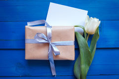 A tulipa da mola floresce, caixa de presente e o cartão de papel na tabela de madeira azul de cima no plano coloca o estilo Fotos de Stock