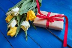 A tulipa da mola floresce, caixa de presente na tabela de madeira azul de cima no estilo da configuração do plano Fotografia de Stock Royalty Free