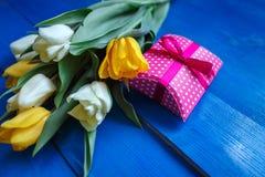 A tulipa da mola floresce, caixa de presente na tabela de madeira azul de cima no estilo da configuração do plano Fotos de Stock Royalty Free