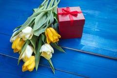 A tulipa da mola floresce, caixa de presente na tabela de madeira azul de cima no estilo da configuração do plano Imagens de Stock
