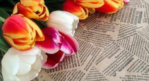 Tulipanów kwiatów wiązka na rocznik gazety tle Zdjęcie Stock