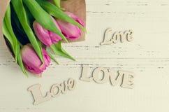 Tulipan kwitnie z drewnianymi słowami miłość Obrazy Royalty Free