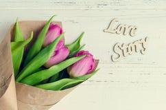 Tulipan kwitnie z drewnianymi słowami LOVE STORY Zdjęcia Royalty Free