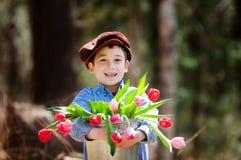 Tulipanes adorables de la explotación agrícola del niño pequeño Imágenes de archivo libres de regalías