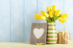 Tulipanes amarillos, caja de regalo y marco en forma de corazón Foto de archivo libre de regalías