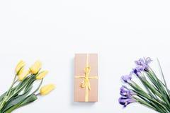 Tulipanes amarillos e iris púrpuras con una caja de regalo en un backg blanco Foto de archivo libre de regalías