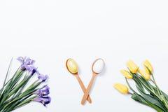 Tulipanes amarillos, iris púrpuras y cuchara dos con los huevos de Pascua en a Imágenes de archivo libres de regalías