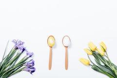 Tulipanes amarillos, iris púrpuras y un par de cuchara con el huevo de Pascua Imagen de archivo