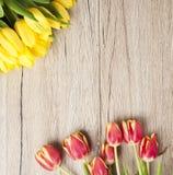 Tulipanes amarillos que mienten en la tabla rústica vieja de madera Foto de archivo libre de regalías