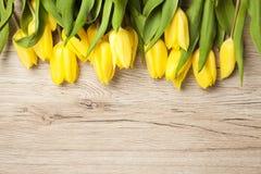 Tulipanes amarillos que mienten en la tabla rústica vieja de madera Fotografía de archivo