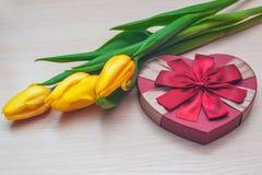 Tulipanes amarillos y regalo hermoso bajo la forma de corazón Fotografía de archivo