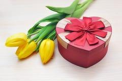 Tulipanes amarillos y regalo hermoso bajo la forma de corazón Foto de archivo