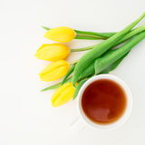 Tulipanes amarillos y taza del té aislada en el fondo blanco Fondo floral Endecha plana Visión superior Imagenes de archivo
