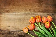 Tulipanes anaranjados sobre la sobremesa de madera Foto de archivo libre de regalías
