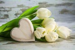 Tulipanes blancos y un corazón de la madera en un backgr de madera gris del vintage Foto de archivo libre de regalías