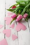 Tulipanes blandos de la primavera con los corazones de papel rosados Fotos de archivo libres de regalías