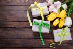 Tulipanes brillantes y cajas amarillos y blancos de la primavera con los presentes encendido Fotografía de archivo libre de regalías