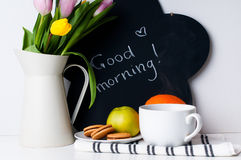 Tulipanes, café de la mañana, fruta y tarjeta de tiza Foto de archivo