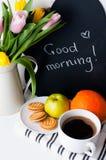 Tulipanes, café de la mañana, fruta y tarjeta de tiza Imagen de archivo
