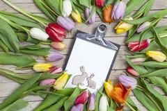 Tulipanes coloreados frescos en frente un fondo de madera con los conejitos de pascua Fotografía de archivo