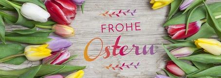 Tulipanes coloreados frescos en frente un fondo de madera con los conejitos de pascua Fotos de archivo