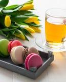 Tulipanes de algunos macarrones y taza amarillos de té en el día de madres de madera de la primavera de la tabla imágenes de archivo libres de regalías
