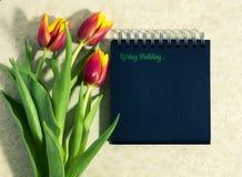 Tulipanes de la primavera con un cuaderno Imagen de archivo libre de regalías