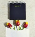Tulipanes de la primavera con un cuaderno Imagen de archivo