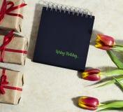 Tulipanes de la primavera con un cuaderno Fotos de archivo