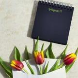 Tulipanes de la primavera con un cuaderno Fotos de archivo libres de regalías