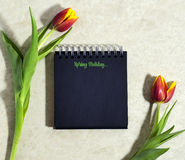 Tulipanes de la primavera con un cuaderno Fotografía de archivo