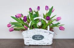 Tulipanes de la primavera en una cesta de mimbre blanca imagen de archivo libre de regalías