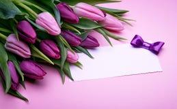 Tulipanes de la primavera y tarjeta de felicitación fotografía de archivo
