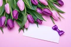Tulipanes de la primavera y tarjeta de felicitación imagenes de archivo