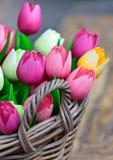 Tulipanes de madera coloridos en una cesta Imagenes de archivo