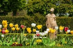 Tulipanes delante de la estatua antigua en la isla del balneario en Piestany SLO Imágenes de archivo libres de regalías