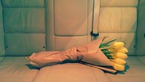 Tulipanes en documento marrón sobre el asiento de carro fotografía de archivo