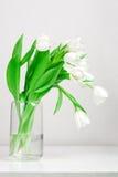 Tulipanes en el florero de cristal Foto de archivo libre de regalías