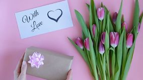 Tulipanes en fondo rosado Mujer que pone la tarjeta de felicitación con el texto CON AMOR y un regalo Directamente sobre la visió almacen de metraje de vídeo