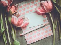 Tulipanes frescos con el corazón, el papel en blanco y el marcador, visión superior imagen de archivo