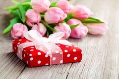 Tulipanes hermosos con la caja de regalo roja del lunar. Imágenes de archivo libres de regalías