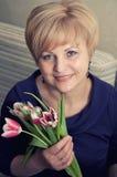 Tulipanes hermosos de la explotación agrícola de la mujer Foto de archivo libre de regalías