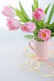 Tulipanes hermosos en un florero con el papel decorativo fotografía de archivo libre de regalías