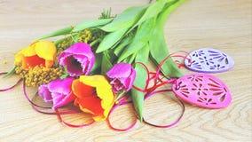 Tulipanes, mimosa y decoraciones de Pascua en fondo de madera Imagen de archivo libre de regalías