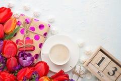 Tulipanes multicolores con los regalos y el café, y un calendario a partir del 13 de mayo en un fondo ligero, visión superior, co foto de archivo libre de regalías