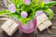 Tulipanes púrpuras con los regalos en la tabla de madera Foto de archivo