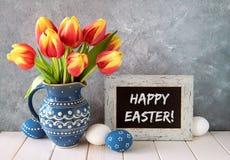 tulipanes Rojo-amarillos en jarra de cerámica azul con los huevos de Pascua y a Fotografía de archivo libre de regalías
