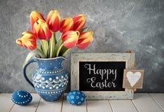 tulipanes Rojo-amarillos en jarra de cerámica azul con los huevos de Pascua y a Imagenes de archivo